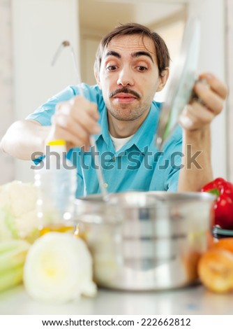 handsome caucasian guy cooking with ladle at kitchen - stock photo