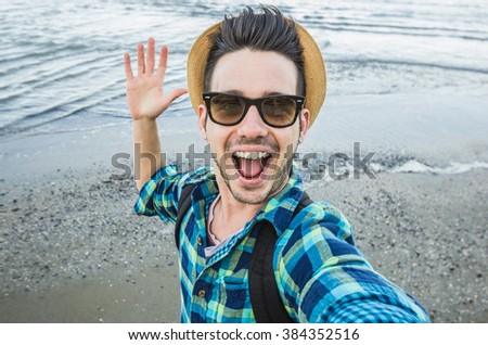 Handsome caucasian guy takes a selfie at the beach - people, lifestyle and technology concept - stock photo
