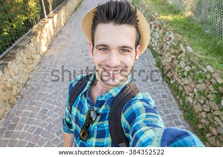 Handsome caucasian guy takes a selfie outdoor - people, lifestyle and technology concept - stock photo