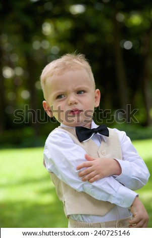 Handsome caucasian little boy in a suit outdoor