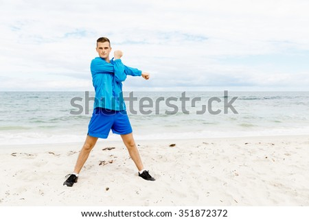 Handsome caucasian male doing exercises on beach - stock photo