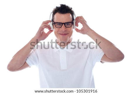 Handsome caucasian male enjoying music  holding his headphones - stock photo