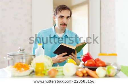 handsome caucasian man doing lunch with cookbook  - stock photo