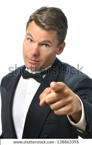 Handsome Caucasian man in black tuxedo points finger at you while raising eyebrows