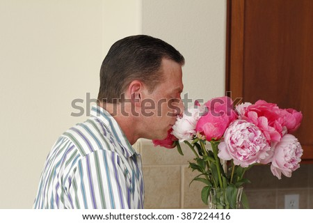 Handsome caucasian man seen from the side smelling a bouquet of pink and red peony flowers in a vase on a kitchen counter. A male smelling peony flowers gift. - stock photo