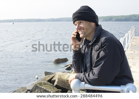 Handsome Caucasian man smiles while talking on cell phone as he leans against railing at end of breakwater of bay in Rockland, Maine - stock photo