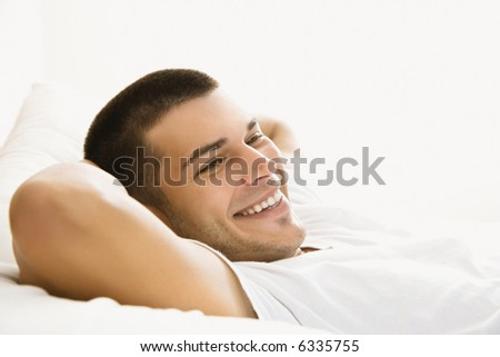 Handsome Caucasian mid adult man lying with hands behind head and smiling. - stock photo