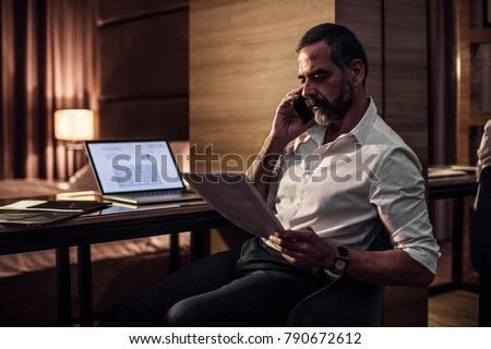 Handsome Caucasian middle-aged businessman talking on cell phone and looking at papers.