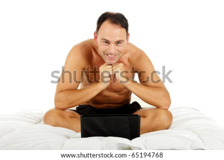 Handsome caucasian middle aged man sitting cross-legged in bed on white sheets, with laptop. Studio shot. White background - stock photo