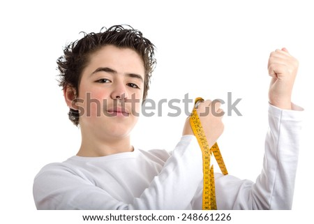 Handsome Caucasian smooth-skinned boy in white long sleeved t-shirt smiles while measuring the muscle of his left arms with yellow meter tape - stock photo