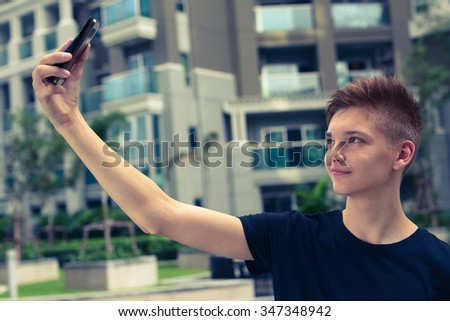 Handsome Caucasian teenager boy outdoors taking selfie picture with mobile phone - stock photo