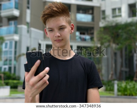 Handsome Caucasian teenager boy outdoors using mobile phone - stock photo