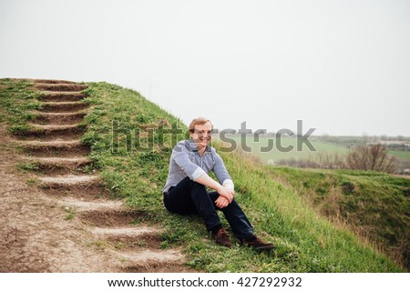 Handsome caucasian young man in casual clothes. He is sitting near the earthen ladder - stock photo