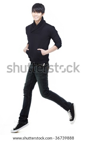 Handsome, charming, young Chinese man running, jogging and jumping. Focus on eyes and face. Intentional motion blur with his left leg to give a sense of movement. - stock photo