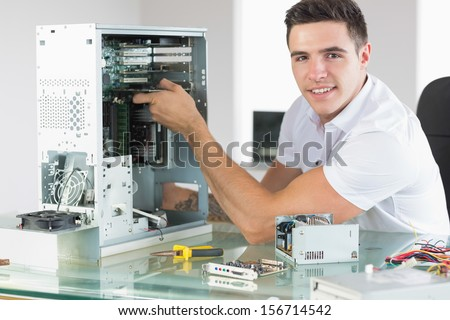 Handsome cheerful computer engineer working at open computer in bright office - stock photo