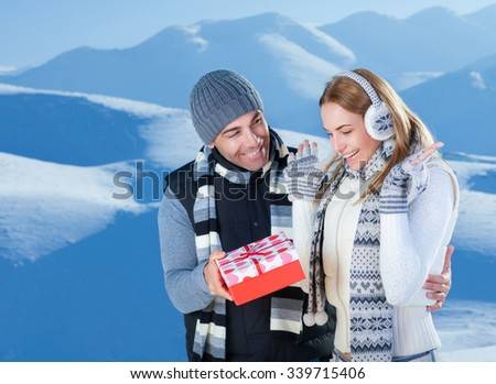 Handsome cheerful man giving to her precious girlfriend red gift box, celebrating Christmas holidays in the beautiful snowy mountains
