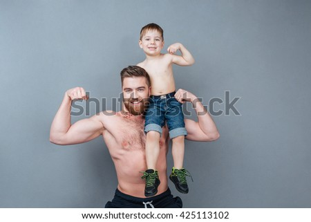 Handsome cheerful strong man holding his little son on his shoulder and showing biceps over grey background - stock photo