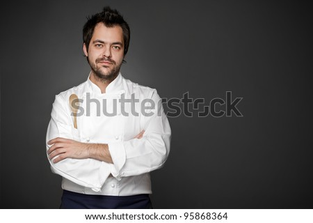 Handsome chef posing against gray background