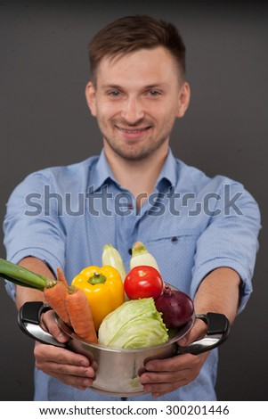 Handsome chef promoting pan with vegetables. He is going to prepare salad with cabbage, carrot, Bulgarian papper, tomatoe etc. - stock photo