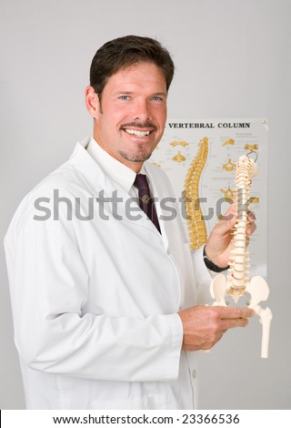 Handsome chiropractor holding plastic replica of a spinal column. - stock photo