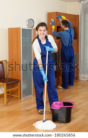 Handsome cleaners team cleaning in living room - stock photo