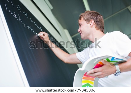 handsome college student solving a math problem during math class in front of the blackboard/chalkboard (color toned image) - stock photo