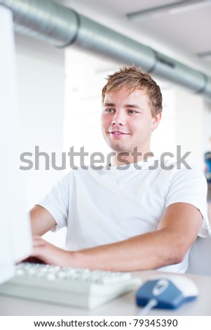 handsome college student using a computer in a college/university library/study room (color toned image) - stock photo