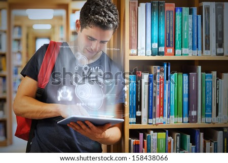Handsome college student working on his digital tablet with futuristic interface in university library - stock photo