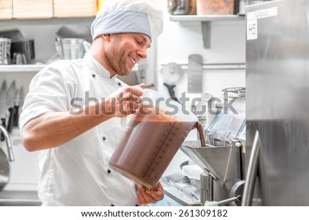 Handsome confectioner in chef uniform producing ice cream with ice