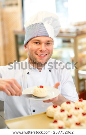 Handsome confectioner putting cake on the plate