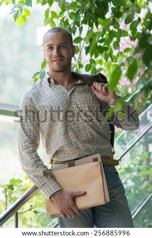 Handsome confident businessman portrait standing on stairs and holding documents - stock photo