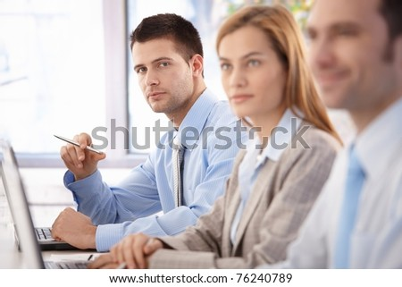 Handsome, confident businessman sitting at meeting room, having training with colleagues.? - stock photo