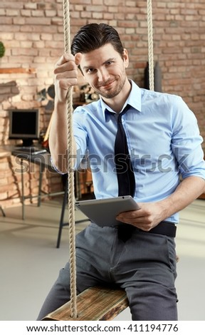 Handsome confident businessman sitting in swing, holding tablet, smiling. - stock photo