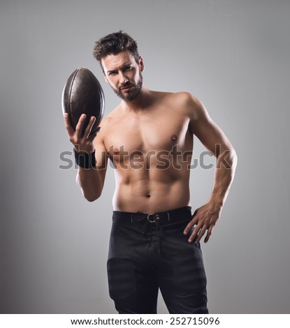 Handsome confident football player holding ball and showing his athletic body - stock photo