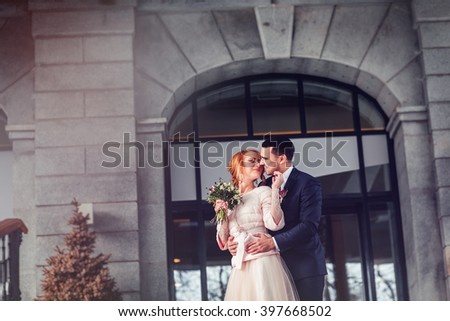 Handsome confident groom and beautiful caucasian bride posing near stone architecture of the hotel with a glass wall arch - stock photo