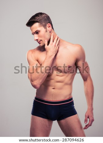 Handsome confident man with muscular body posing over gray background - stock photo