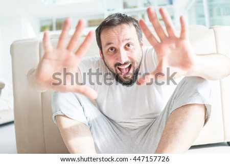 Handsome confident young man relaxing at home on the sofa looking at the camera with a friendly smile - stock photo