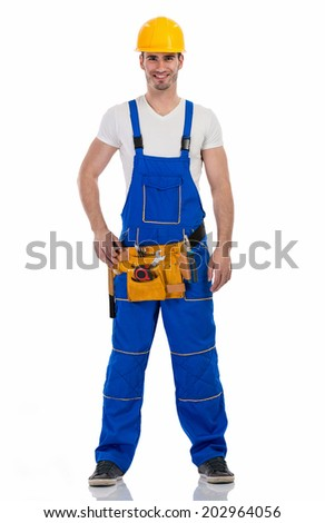 Handsome  construction worker with tool-belt, full length - stock photo