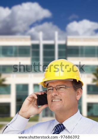 Handsome Contractor in Hardhat and Necktie Smiles as He Talks on His Cell Phone in Front of Building. - stock photo