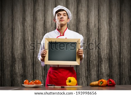 Handsome cook holding blank chalk board. Place for text - stock photo