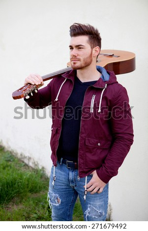 Handsome cool man carrying a guitar on his shoulders - stock photo
