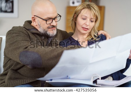 Handsome couple seated on couch in their living room with paperwork and binder making plans - stock photo