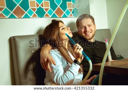 Handsome couple smokes shisha in the hookah bar and having fun - stock photo