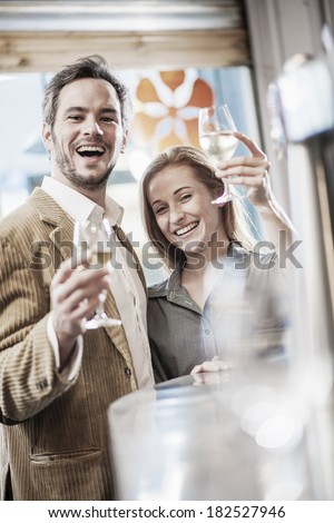 handsome couple toasting in a bar looking at camera - stock photo