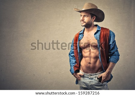 handsome cowboy with hat and open shirt - stock photo