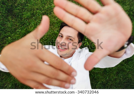 Handsome cute happy groom hands gesture while lying on grass closeup