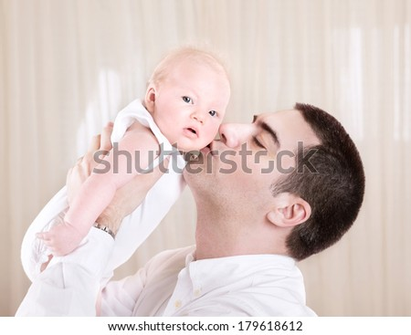 Handsome daddy kissing cute little toddler, man enjoying time spend with his little newborn daughter at home, love concept  - stock photo