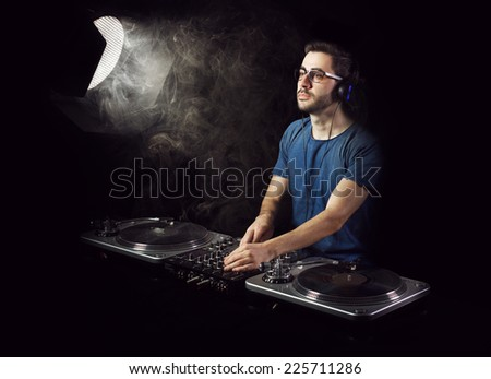 Handsome deejay in blue shirt playing music from vinyl. He is illuminated through smoke by a vintage spot light reflector.