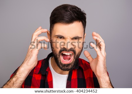 Handsome depressed young man screaming and showing hands