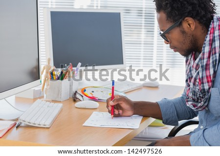 Handsome designer drawing something with a red pencil in a modern office - stock photo